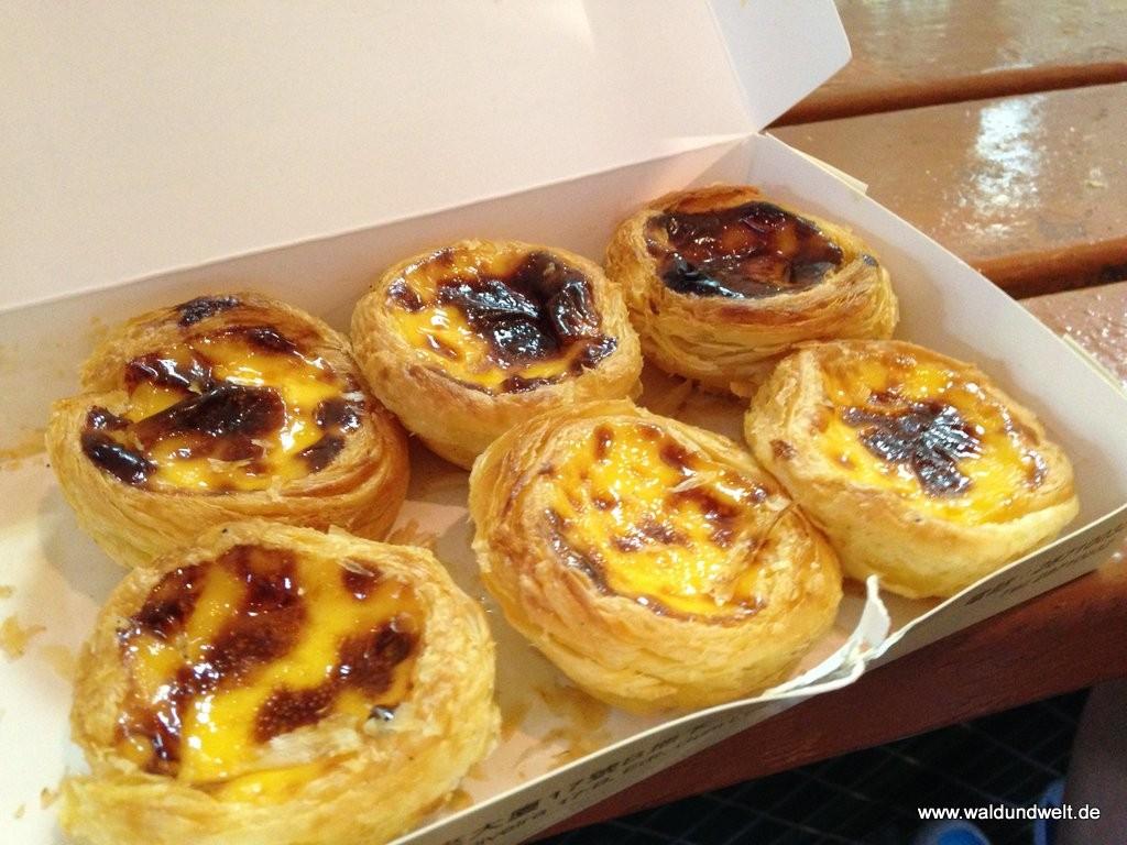 Ein kulinarisches Must Have in Macau: Die portugisischen Egg Tarts sind der absolute Knaller. Vor allem in kleineren Läden, wo die Schlangen vor der Tür recht lang sind, schmeckt die süße Verführung einfach phänomenal. Die Landsfrauen und -männer in Hongkong versuchen sich zwar auch vielerorts an der Spezilität, doch an die Qualität Macaus kommt man auf der anderen Seite der Bucht schwerlich ran.