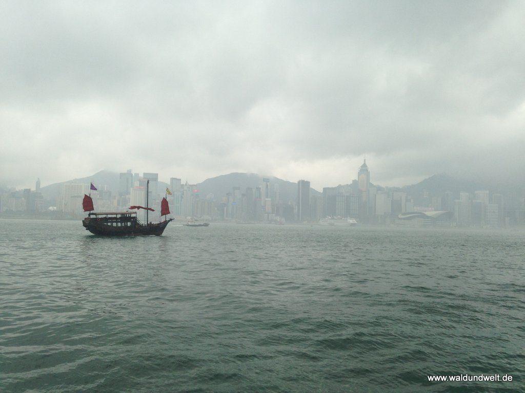 Nebelverhangene Skyline von Hong Kong Island mit chinesischem Boot im Vordergrund